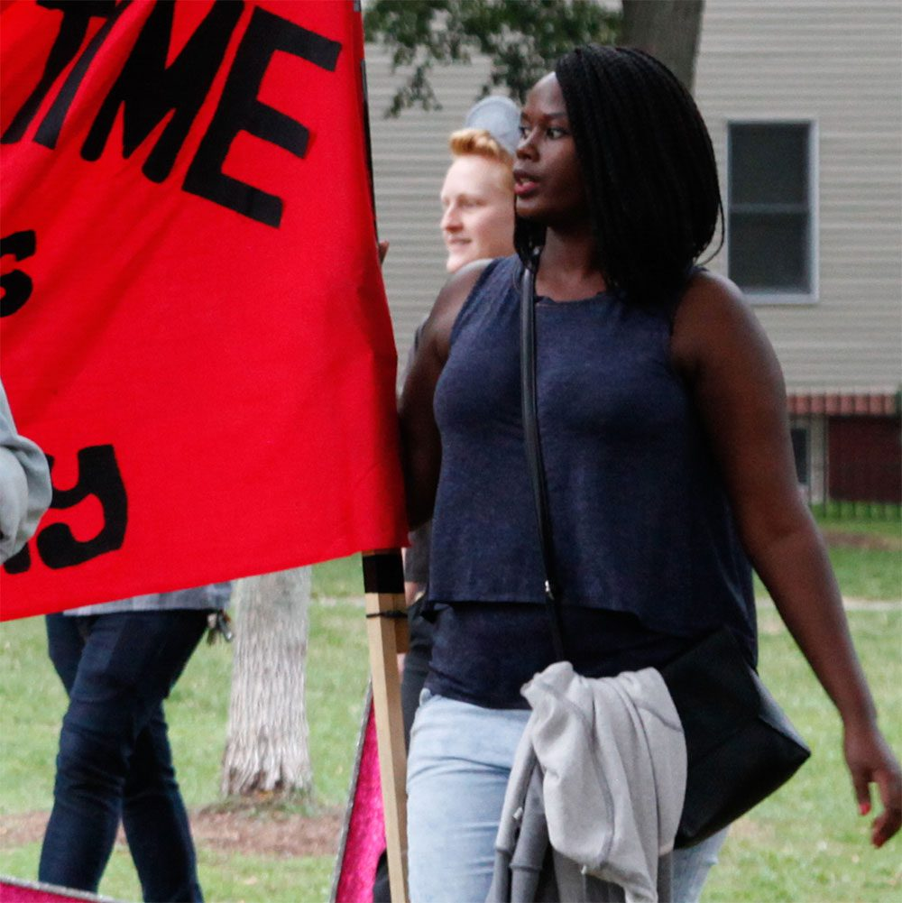 A young black woman walks and holds a red racial equality flag